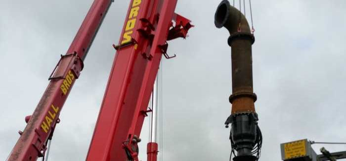 The smaller of the two pumps being lifted into position