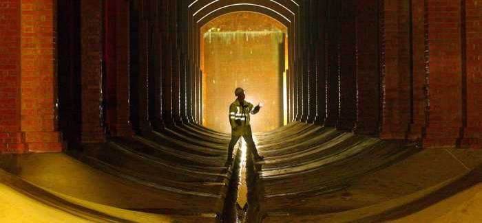 An engineer surveying an underground reservoir at Honor Oak, London