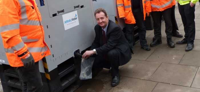 Ealing council leader Julian Bell fills a sachet from the emergency bowser