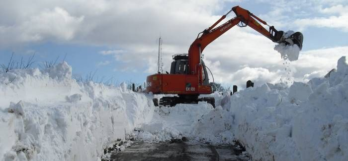 A tracked digger clearing the road to Slimero service reservoir, County Antrim, during exceptional snowfall in March